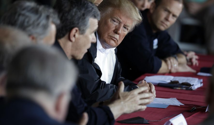 President Donald Trump listens as North Carolina Gov. Roy Cooper speaks while attending a briefing, after arriving at Marine Corps Air Station Cherry Point to visit areas impacted by Hurricane Florence, Wednesday, Sept. 19, 2018, in Havelock, N.C. FEMA Administrator Brock Long is leaning in a right.  (AP Photo/Evan Vucci)