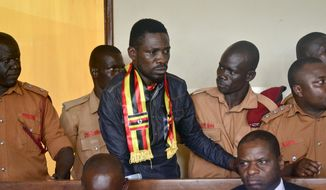 FILE - In this Thursday, Aug. 23, 2018 file photo, Ugandan pop star-turned-lawmaker Kyagulanyi Ssentamu, also known as Bobi Wine, center, arrives at a magistrate's court in Gulu, northern Uganda. Wine is due to return home on Thursday, Sept. 20, 2018 after seeking treatment in the United States for injuries suffered during alleged state torture. (AP Photo, File)