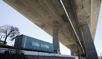 In this July 2, 2018, file photo, a truck carrying a cargo container drives under the Gerald Desmond Bridge under construction in Long Beach, Calif. China on Tuesday, Sept. 18, 2018, announced a tariff hike on $60 billion of U.S. products in response to President Donald Trump's latest duty increase in a dispute over Beijing's technology policy. (AP Photo/Jae C. Hong, File)