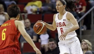 FILE - In this April 26, 2018, file photo, United States' Sue Bird, right, dribbles as China's Lili Wang defends during the first half of an exhibition basketball game in Seattle. Bird is on a record fifth U.S. women's basketball World Cup team.  The veteran guard will try and help the Americans win a third straight FIBA Women's Basketball World Cup title and in the process her unprecedented fourth gold medal in the tournament. (AP Photo/Elaine Thompson, File)