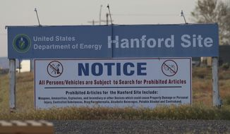 FILE - In this May 9, 2017, file photo, signs are posted by the Hanford Nuclear Reservation in Benton County in Richland, Wash. The U.S. government will pay $925,000 and improve worker safety to settle a lawsuit over employee exposure to chemical vapors at the nation's most polluted nuclear weapons production site. Washington state Attorney General Bob Ferguson said Wednesday, Sept. 19, 2018, that the U.S. Energy Department will test new technology to capture and destroy dangerous vapors that escape from nuclear waste storage tanks at Hanford Nuclear Reservation. (AP Photo/Manuel Valdes, File)