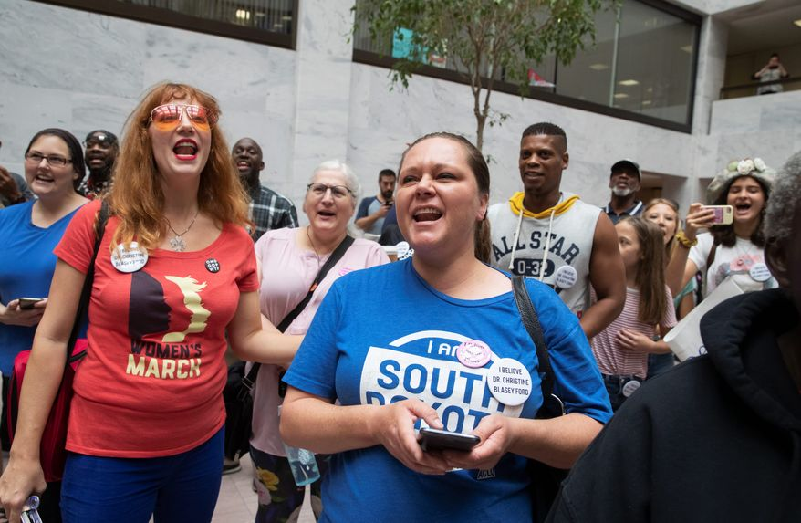 Protesters opposed to President Trump's Supreme Court nominee, Judge Brett M. Kavanaugh, demonstrate in the Hart Senate Office Building on Capitol Hill. (Associated Press)