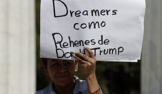"""A woman holds up signs reading in Spanish: """"Dreamers as prisoners of Donald Trump,"""" and """"Stop deportations that separate families, causing pain, anguish, and tears"""", as a handful of demonstrators protested outside the Ministry of Foreign Relations, where U.S. Secretary of State Rex Tillerson was meeting with his Mexican and Canadian counterparts in Mexico City, Friday, Feb. 2, 2018. Tillerson's Mexico stop kicks off a weeklong trip to Latin America which will take him to Argentina, Peru, and Colombia, with a final stop in Jamaica. (AP Photo/Rebecca Blackwell)"""