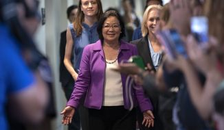 Sen. Mazie Hirono, D-Hawaii, flanked by Sarah Burgess, left, an alumnae of the Holton Arms School, and Sen. Kirsten Gillibrand, D-N.Y., right, is applauded by demonstrators as they arrive to speak to reporters in support of professor Christine Blasey Ford, who is accusing Supreme Court nominee Brett Kavanaugh of a decades-old sexual attack, during a news conference on Capitol Hill in Washington, Thursday, Sept. 20, 2018. Christine Blasey Ford was a student at the Holton Arms School, a Maryland all-girls school, in the early 1980s. (AP Photo/J. Scott Applewhite)