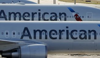 "FILE - In this Nov. 6, 2017, file photo, a pair of American Airlines jets are parked on the airport apron at Miami International Airport in Miami. American Airlines is threatening to prohibit customers from making changes to nonrefundable tickets if Congress makes good on a proposal to crack down on unreasonable airline fees. American CEO Doug Parker says his airline would be acting just like many other businesses when customers want to swap their ticket for a different flight or for another day. ""We - like the baseball team, like the opera - would say, 'We're sorry, it was nonrefundable,'"" Parker said this week.  (AP Photo/Wilfredo Lee, File)"