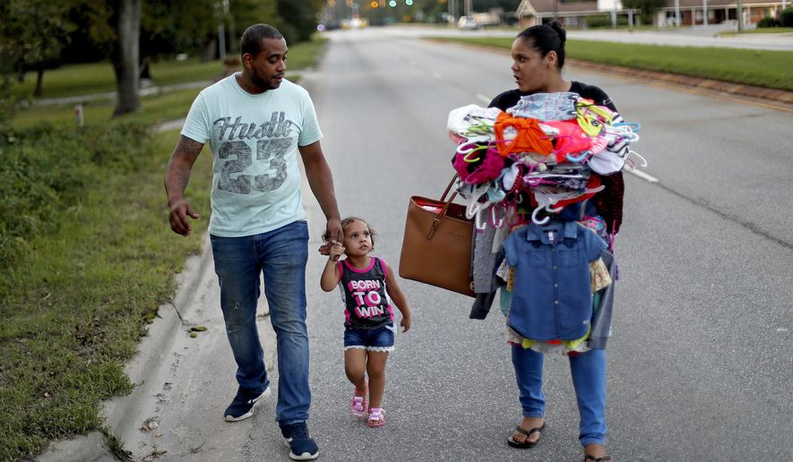 "Jose Perez-Santiago, left, and Rosemary Acevedo-Gonzalez, walk with their daughter Jordalis, 2, after retrieving her clothing upon returning to their home for the first time since it was flooded in the aftermath of Hurricane Florence in Spring Lake, N.C., Wednesday, Sept. 19, 2018. ""I didn't realize we would lose everything,"" said Perez-Santiago. ""We'll just have to start from the bottom again."" (AP Photo/David Goldman)"