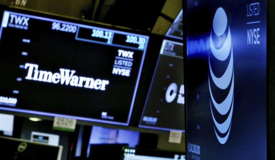 FILE - In this June 13, 2018, file photo, the logos for Time Warner and AT&T appear above alternate trading posts on the floor of the New York Stock Exchange. Defending court approval of its huge merger with Time Warner, AT&T is arguing the Trump Justice Department failed to show that the merger will raise wholesale prices for pay-TV programming and for consumers. (AP Photo/Richard Drew, File)