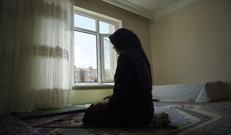 In this Aug. 20, 2018, photo, Meripet, 29, prays at her home in Istanbul, Turkey. Meripet came to Turkey in February 2017 to visit her sick father, leaving four children behind. While in Turkey, she heard Uighur passports were being seized and that people who had gone abroad were being taken to reeducation, so she stayed in Turkey, giving birth to Abduweli. She hasn't seen her other four children since, and heard they were taken to a live-in kindergarten in Hotan, China. (AP Photo/Dake Kang)