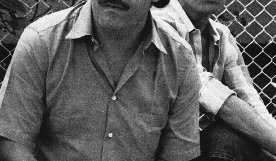 FILE - In this 1983 file photo, Medellin drug cartel boss Pablo Escobar watches a soccer game in Medellin, Colombia. Colombian police announced Thursday, Sept. 20, 2018 that they have shut down a small makeshift museum that showcased the life and times of notorious drug lord, saying the building's managers do not have a tourism license.  The site was managed by Escobar's 71-year-old brother, Roberto. (AP Photo, File)