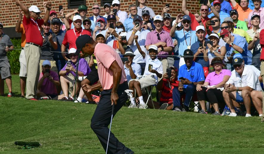 RETRANSMISSION TO CORRECT FROM A BIRDIE TO AN EAGLE - Tiger Woods reacts as he makes a eagle putt on the 18th green during the first round of the Tour Championship golf tournament Thursday, Sept. 20, 2018, in Atlanta. (AP Photo/John Amis)