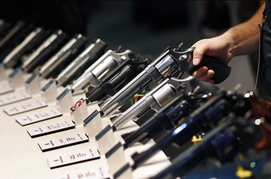 FILE - In this Jan. 19, 2016 file photo, handguns are displayed at the Shooting, Hunting and Outdoor Trade Show in Las Vegas. Proponents of a voter-approved gun buyer screening initiative that passed in 2016 but was never enacted want the Nevada Supreme Court to overrule a judge who decided the measure was fatally flawed and couldn't be enforced. (AP Photo/John Locher, File)