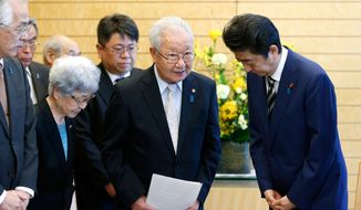 In this March 30, 2018, file photo, Japanese Prime Minister Shinzo Abe, right, meets with Shigeo Iizuka, second from right, leader of a group of families of Japanese abducted by North Korea, and Sakie Yokota, second from left, mother of Megumi Yokota, one of the Japanese abductees and other members at Abe's official residence in Tokyo. (Toru Hanai/Pool Photo via AP, File)