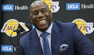 "In this Tuesday, June 26, 2018 file photo,Los Angeles Lakers president of basketball operations, Earvin ""Magic"" Johnson, smiles as he introduces new draft players, Moritz Wagner, originally from Germany, and guard Sviatoslav Mykhailiuk, originally from Ukraine, at the UCLA Health Training Center in El Segundo, Calif. (Associated Press)"