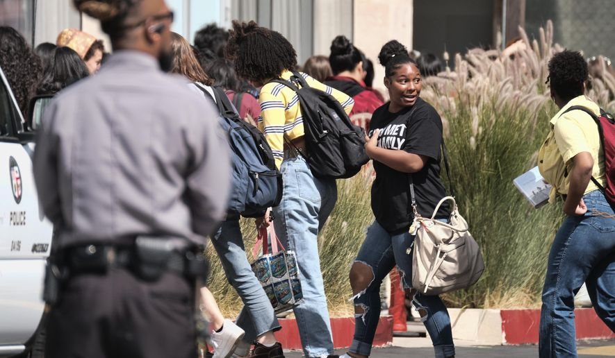Students from Champs Charter High School are moved from one school building to another building on the campus after a shooting in the Van Nuys section of Los Angeles on Thursday, Sept. 20, 2018. Los Angeles police say a shooting near a charter high school wounded a male teenage student and a female school employee. Sgt. Barry Montgomery says he cannot immediately say whether the victims were targeted in the shooting Thursday at a Jack in the Box restaurant across the street from the school. A Fire Department spokesperson said both victims have extremity wounds and were transported to a hospital in stable condition. (AP Photo/Richard Vogel)