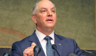 Gov. John Bel Edwards talks about an expected $300 million-plus surplus Louisiana will have from the last budget year, while Commissioner of Administration Jay Dardenne and Revenue Secretary Kimberly Robinson listen to his remarks, on Thursday, Sept. 20, 2018, in Baton Rouge, La. (AP Photo/Melinda Deslatte)