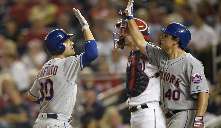 New York Mets' Michael Conforto, left, celebrates his two-run home run with Jason Vargas (40), next to Washington Nationals catcher Matt Wieters during the third inning of a baseball game Thursday, Sept. 20, 2018, in Washington. (AP Photo/Nick Wass)