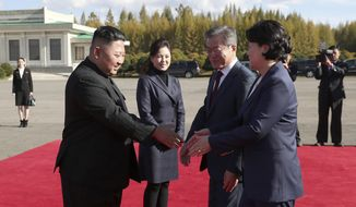 North Korean leader Kim Jong Un, left, flanked by his wife Ri Sol Ju, second from left, bids farewell to South Korean President Moon Jae-in, second from right, and his wife Kim Jung-sook, at Samjiyon airport, in North Korea, Thursday, Sept. 20, 2018. A beaming South Korean President Moon, freshly returned home Thursday from a whirlwind three-day summit with Kim Jong Un, said the North Korean leader wants the U.S. secretary of state to visit Pyongyang soon for nuclear talks, and also hopes for a quick follow-up to his June summit with President Donald Trump. (Pyongyang Press Corps Pool via AP)