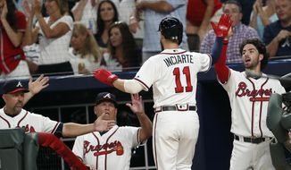 Atlanta Braves from left; bench coach Walt Weiss, manager Brian Snitker, and shortstop Dansby Swanson greet Ender Inciarte (11) at the dugout after scoring on a Atlanta Braves right fielder Nick Markakis base hit in the first inning of a baseball game against the Philadelphia Phillies Thursday, Sept. 20, 2018, in Atlanta. (AP Photo/John Bazemore)