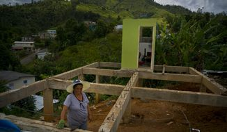 "In this Sept. 8, 2018 photo, Alma Morales Rosario poses for a portrait between the beams of her home being rebuilt after it was destroyed by Hurricane Maria one year ago in the San Lorenzo neighborhood of Morovis, Puerto Rico. Rosario, who is incapacitated by diabetes and a blood disease, took a loan to upgrade her home before the storm hit, and lost everything. After the storm, Rosario rented a home until she could no longer afford it on her monthly $598 dollar pension and now splits her time living with her mother and daughter. Rosario said she already spent her $7,000 dollars of FEMA aid, and is now using money from a relative, who is also helping her with the labor of rebuilding her home, but says she knows there's not enough money for all the materials. ""I hope with God's help to have the house closed on the outside, walls and ceiling in November. But if it's not possible, I'll make a room with the wood I have under the structure and live there until I can finish it. I never thought this was going to happen to me,"" she said. (AP Photo/Ramon Espinosa)"