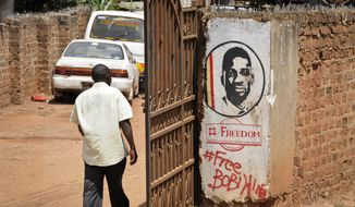 A man walks past graffiti in support of pop star-turned-opposition lawmaker Bobi Wine, whose real name is Kyagulanyi Ssentamu, in the Kamwokya neighborhood where he has many supporters, in Kampala, Uganda Thursday, Sept. 20, 2018. Security forces took Bobi Wine into custody when he arrived from the United States on Thursday, angering his supporters, while authorities barred public gatherings. (AP Photo/Ronald Kabuubi)