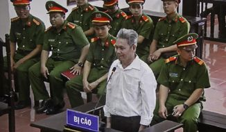 In this Wednesday, Sept. 19, 2018, photo, activist Dao Quang Thuc stands trial in Hoa Binh, Vietnam. He was sentenced to 14 years in prison after being convicted of attempting to overthrow the government by the People's Court in Hoa Binh province Wednesday. (Vu Thi Ha/ Vietnam News Agency via AP)