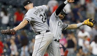 Chicago White Sox's Matt Davidson (24) and Yolmer Sanchez celebrate the team's 5-4 win against the Cleveland Indians in a baseball game Thursday, Sept. 20, 2018, in Cleveland. (AP Photo/Tom E. Puskar)