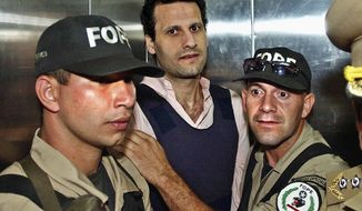 FILE - In this Nov. 17, 2003 file photo, Lebanese citizen Assad Ahmad Barakat, who was then facing tax evasion charges, is escorted by police to a courthouse in Asuncion, Paraguay. On Friday, Sept. 21, 2018, federal police in Brazil arrested Barakat, a fugitive accused of belonging to Lebanon's Hezbollah militia and of being a key financier of terrorism.  (AP Photo/Jorge Saenz, File)