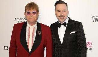 FILE - In this Sunday, March 4, 2018 file photo,  Elton John, left, and David Furnish arrive at the 2018 Elton John AIDS Foundation Oscar Viewing Party, in West Hollywood, Calif. Singer Elton John and partner David Furnish have accepted an apology and undisclosed libel damages over a newspaper report that their dog severely injured a child while on a play date.  (Photo by Willy Sanjuan/Invision/AP, File)