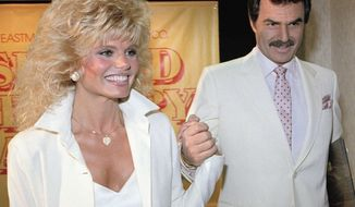 FILE - In this March 27, 1987 file photo, Burt Reynolds, right, holds hands with Loni Anderson at luncheon in Los Angeles. Reynolds' friends and relatives shared memories of the late actor at a private memorial service. A family spokeswoman says Reynolds' ex-wife Anderson and their son Quinton Anderson Reynolds were among the speakers at the Thursday, Sept. 20, 2018, service at Quattlebaum Funeral Home in North Palm Beach, Fla. (AP Photo/Bob Galbraith, File)