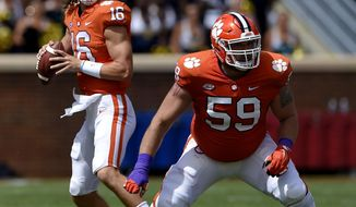 FILE - In this Saturday, Sept. 15, 2018, file photo, Clemson quarterback Trevor Lawrence drops back to pass with blocking help from Gage Cervenka (59) during the first half of an NCAA college football game against Georgia Southern in Clemson, S.C. The Tigers remain committed to playing both incumbent starter Kelly Bryant and highly rated freshman Trevor Lawrence as they head into Saturday's Atlantic Coast Conference opener against struggling Georgia Tech.  (AP Photo/Richard Shiro, File)