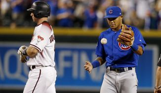Chicago Cubs shortstop Addison Russell, right, flips the ball in the air after tagging out Arizona Diamondbacks' Paul Goldschmidt, left, trying to steal second base for the final out during the ninth inning of a baseball game, Monday, Sept. 17, 2018, in Phoenix. The Cubs defeated the Diamondbacks 5-1. (AP Photo/Ross D. Franklin)