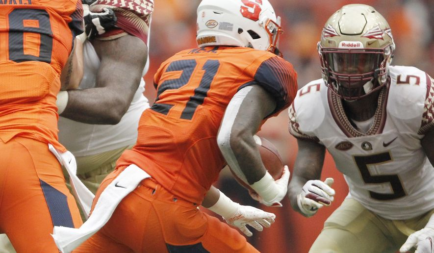 Florida State's Marvin Wilson, back left, and Dontavious Jackson, right, look to tackle Syracuse's Moe Neal, center, in the second quarter of an NCAA college football game in Syracuse, N.Y., Saturday, Sept. 15, 2018. Syracuse beat Florida State 30-7. (AP Photo/Nick Lisi)