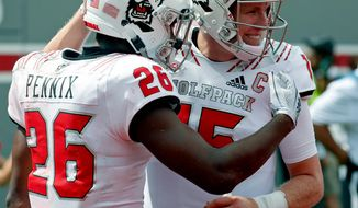 North Carolina State's Trent Pinnix (26) celebrates his touchdown with Ryan Finley (15) after he scored during the second half of an NCAA college football game in Raleigh, N.C., Saturday, Sept. 8, 2018. (AP Photo/Chris Seward)