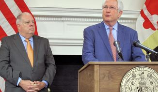 Maryland Insurance Commissioner Al Redmer and Gov. Larry Hogan, left, announce lower health insurance premiums for individual plans on Maryland's health care exchange on Friday, Sept. 21, 2018 in Annapolis.  (AP Photo/Brian Witte)
