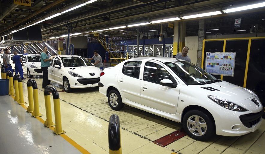 In this Sunday, Sept. 9, 2018 photo, a line of Peugeot cars rolls out at the state-run Iran Khodro automobile manufacturing plant, just outside Tehran, Iran. As Iran's rial currency suffers precipitous falls against the U.S. dollar, cars are growing more and more expensive. Meanwhile, foreign manufacturers are pulling out from the country and foreign-produced parts are becoming harder to find. That's a problem for one of the Mideast's biggest countries and home to 80 million people. (AP Photo/Ebrahim Noroozi)