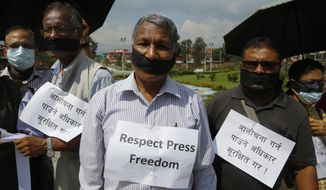 """In this Sept. 19, 2018 photo,  Nepalese journalists stage a protest against a new set of laws that threaten to curb the media in Kathmandu, Nepal. Placards read, """"Secure the rights to criticize"""". (AP Photo/Niranjan Shrestha)"""