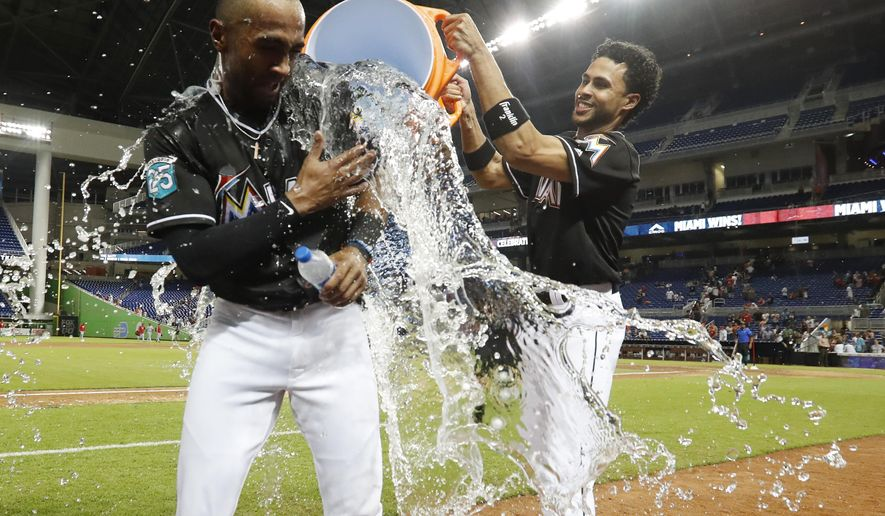 Miami Marlins' Yadiel Rivera, right, douses Isaac Galloway as Galloway is interviewed after the team defeated the Cincinnati Reds in 10 innings of a baseball game, Friday, Sept. 21, 2018, in Miami. (AP Photo/Wilfredo Lee)