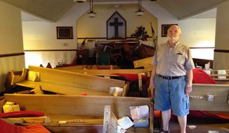 Pastor Floyd Benfield stands in front of the flood-damaged sanctuary of the Presbyterian Church of the Covenant in Spring Lake, N.C., Thursday, Sept. 20, 2018. Just days before, the flooding Little River had left the church half submerged. (AP Photo/Alex Derosier)