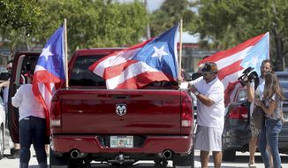 People gather in the parking lot and get ready to head to West Palm Beach for a protest, Saturday, Sept. 22, 2018, in Hollywood, Fla.  Activists marking the one-year anniversary of Hurricane Maria's devastation of Puerto Rico are staging a rally and caravan focused on President Donald Trump's Mar-a-Lago resort in Florida. (Mike Stocker/South Florida Sun-Sentinel via AP)