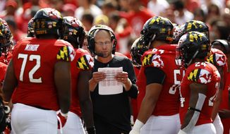 Maryland interim head coach Matt Canada, center, huddles with players in the first half of an NCAA college football game against Minnesota, Saturday, Sept. 22, 2018, in College Park, Md. (AP Photo/Patrick Semansky) **FILE**