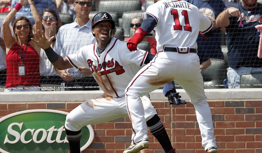 Atlanta Braves' Ronald Acuna Jr., left, and Ender Inciarte (11) celebrate after scoring on a two-run base hit by Freddie Freeman in the second inning of a baseball game against the Philadelphia Phillies, Saturday, Sept. 22, 2018, in Atlanta. (AP Photo/John Bazemore)