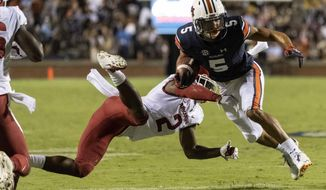 Auburn wide receiver Anthony Schwartz (5) runs a sweep in the red zone as Arkansas defensive back Kamren Curl (2) hits him during the first half of an NCAA college football game, Saturday, Sept. 22, 2018, in Auburn, Ala. (AP Photo/Vasha Hunt)0