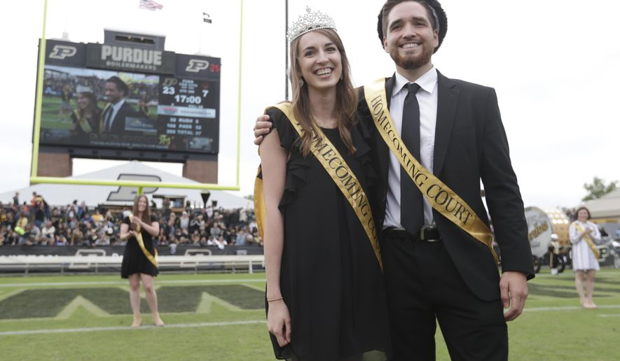 """Grant Wood and Lily Bishop pose after being named """"Royalty"""" as part of Purdue's first gender-neutral homecoming court during halftime of an NCAA college football game between Purdue and Boston College in West Lafayette, Ind., Saturday, Sept. 22, 2018. The school eliminated the titles of king and queen and students cast two votes for """"royalty"""". (AP Photo/Michael Conroy)"""