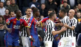 Crystal Palace's Wilfried Zaha, centre, is held back by teammates as he clashes with Newcastle United's Kenedy, during the English Premier League soccer match between Crystal Palace and Newcastle United, at Selhurst Park, in London, Saturday, Sept. 22, 2018.(Jonathan Brady/PA via AP)