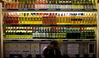 FILE- In this Nov. 27, 2012 file photo, a customer checks bottles of imported wine at a supermarket in Beijing. The World Health Organization said in a report published Friday Sept. 21, 2018,  that drinking too much alcohol killed more than 3 million people in 2016, mostly men, with Europe having the highest global per capita alcohol consumption.  (AP Photo/Alexander F. Yuan, FILE)
