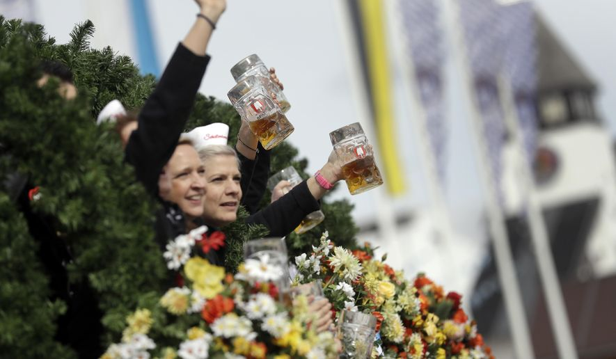 People lift beer glasses during a parade as part of the opening of the 185th 'Oktoberfest' beer festival in Munich, Germany, Saturday, Sept. 22, 2018. The world's largest beer festival will be held from Sept. 22 until Oct. 7, 2018. (AP Photo/Matthias Schrader)
