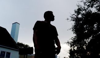"""In this Friday, Sept. 14, 2018 photo, Adan, a 27-year-old Guatemalan living in south Florida, who did not wish to be further identified, poses for a photo near his home. Immigrant families hoping to reunite with children and teenagers who crossed the border alone are facing an intimidating system that includes submitting fingerprints by all adults in the household where a migrant child will live. Adan followed the process to gain custody of his 17-year-old sister in detention. Now, he wants to leave his apartment. """"I feel I need to move to have a sense of security,"""" said the landscaper about ICE knowing where he lives. (AP Photo/Wilfredo Lee)"""