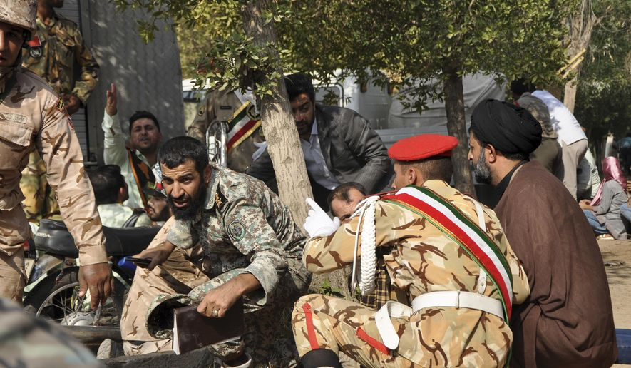 In this photo provided by the Iranian Students' News Agency, ISNA, Iranian armed forces members and civilians take shelter in a shooting during a military parade marking the 38th anniversary of Iraq's 1980 invasion of Iran, in the southwestern city of Ahvaz, Iran, Saturday, Sept. 22, 2018. Gunmen attacked the military parade, killing at least eight members of the elite Revolutionary Guard and wounding 20 others, state media said. (AP Photo/ISNA, Behrad Ghasemi)