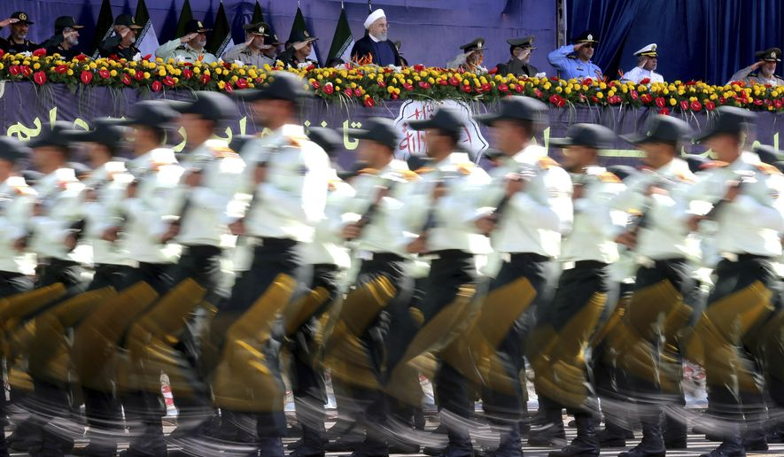 Iran's President Hassan Rouhani, top centre, reviews army troops marching during the 38th anniversary of Iraq's 1980 invasion of Iran, in front of the shrine of the late revolutionary founder, Ayatollah Khomeini, outside Tehran, Iran, Saturday, Sept. 22, 2018.  Gunmen attacked the military parade, killing at least eight members of the elite Revolutionary Guard and wounding 20 others, state media said. (AP Photo/Ebrahim Noroozi)