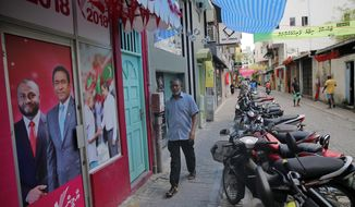 A Maldivian man walks past an election campaign office of Maldivian President Yameen Abdul Gayoom and his running mate Mohamed Shaheem Ali Saeed in Male, Maldives, Saturday, Sept. 22, 2018. Yameen's only contender in Sunday's election is longtime lawmaker Ibrahim Mohamed Solih, backed by former President Mohamed Nasheed who is now living in exile in neighboring Sri Lanka. (AP Photo/Eranga Jayawardena)